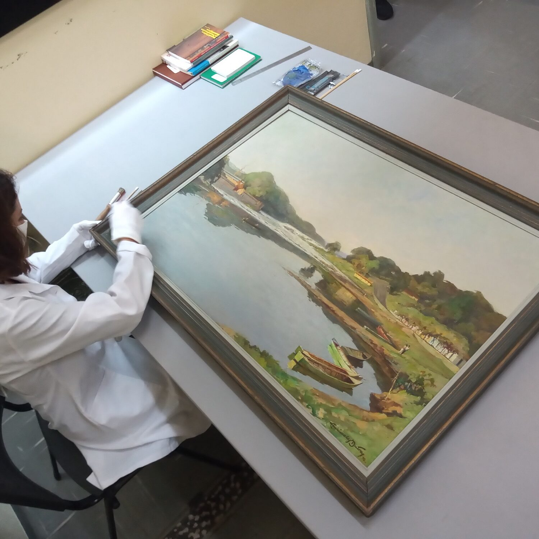 Ana, especialista, faz conservação em tela de Archimedes Dutra, de 1975. Divulgação